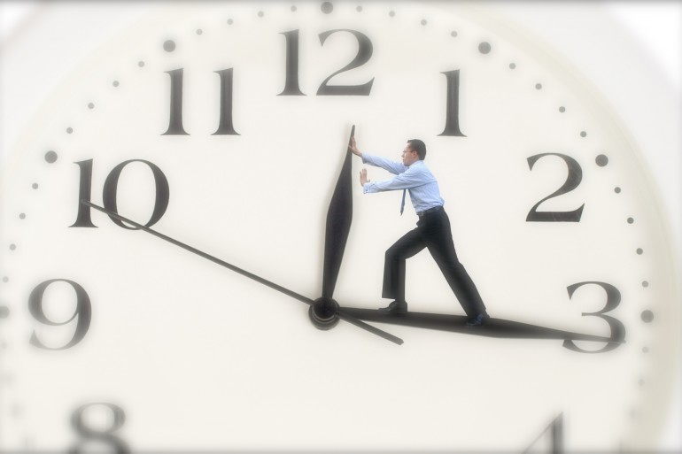clock hands being pushed back by a business man